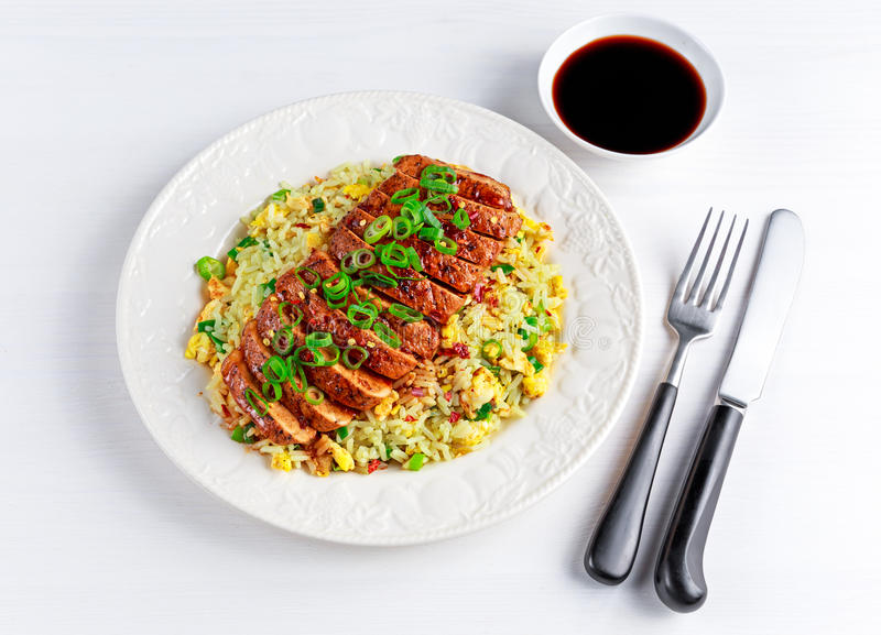 Chinese style Egg fried rice with sliced pork fillet on white wooden table. royalty free stock photography