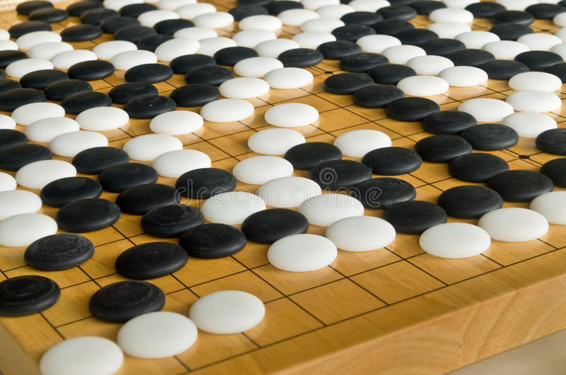 Chinese style Go pieces on wooden board. Close up of Chinese style stone pieces, stones with curve on one side and flat on the other side, on wooden Go board stock photo