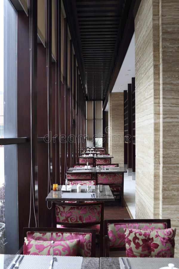 Hotel lobby bar. Purple flocking chair, table near the window stock photography