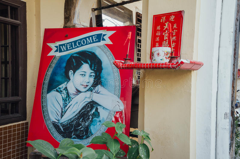 Chinese style illustrator woman in oval frame in front of hostel in George Town. Penang, Malaysia.  stock photos