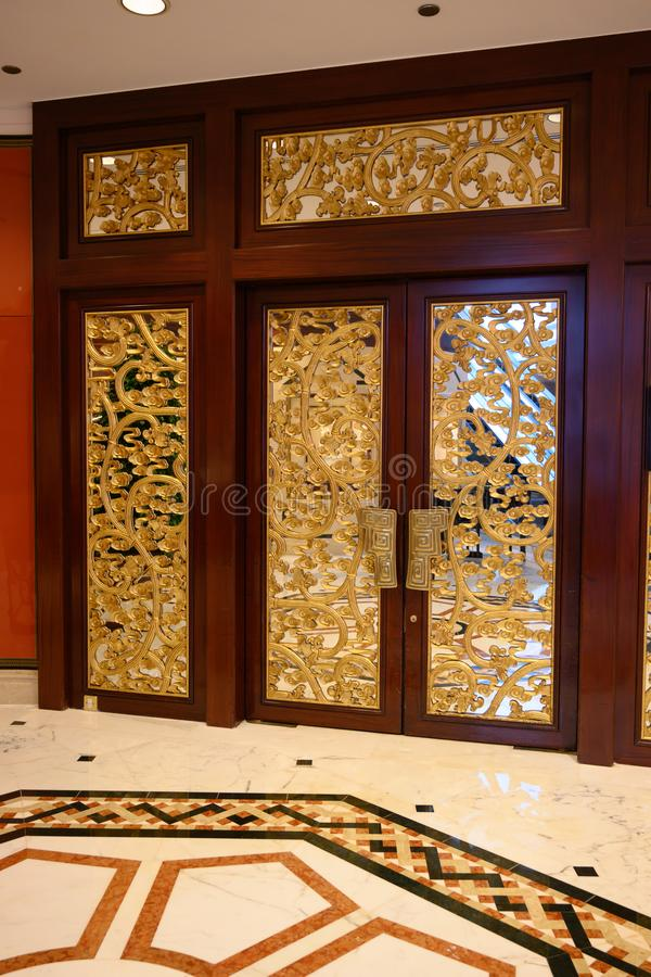 Chinese style luxury golden door with ornamental pattern. Blooms on entrance door to restaurant in Hotel Shangri-La, Hong Kong stock images