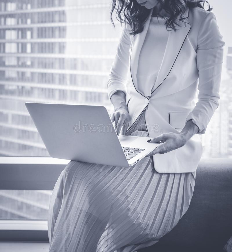 Chinese successful and satisfied businesswoman is standing with laptop computer in modern office interior near skyscraper window stock photo