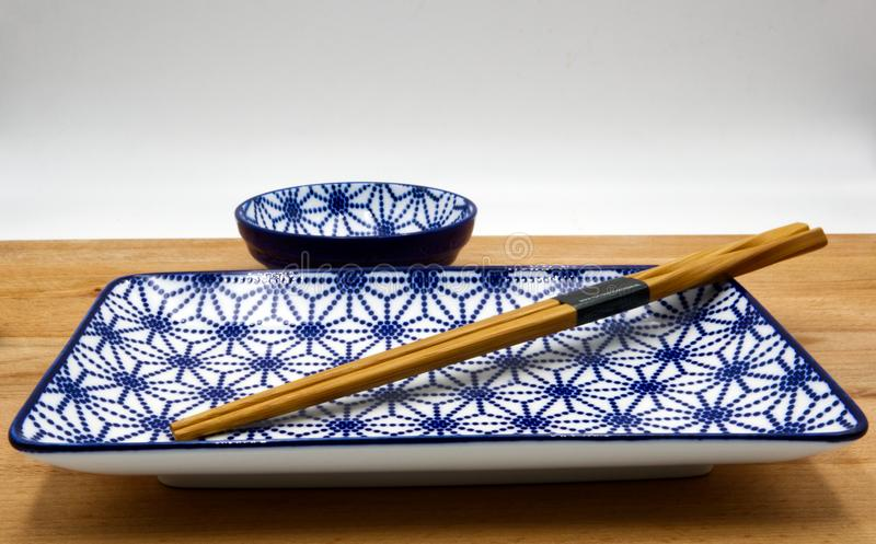 Chinese table set. Wooden chopsticks, chinese bowl and a jar on wooden table, white background stock photography