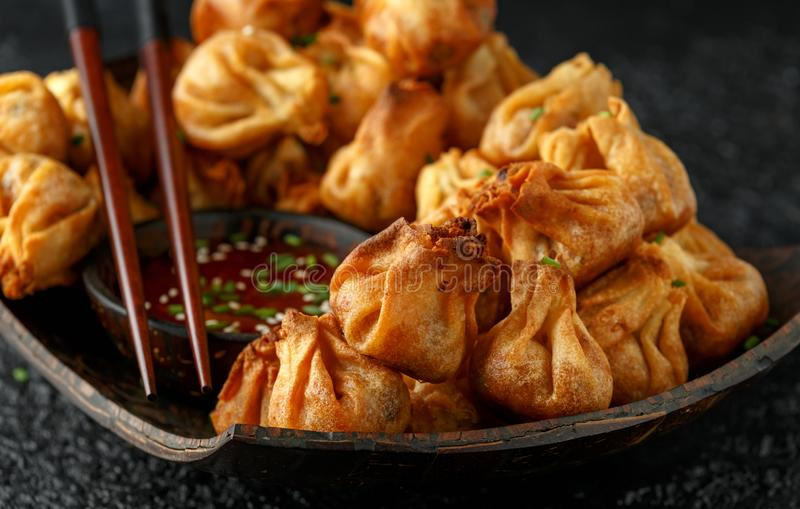 Chinese takeaway finger food Vegetable wontons with sweet chilli dip sauce and chop sticks.  stock photo