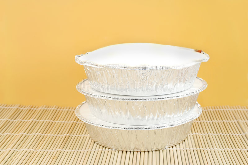 Chinese takeout. Chinese food delivery or takeout aluminum covered containers on bamboo placemat royalty free stock photography