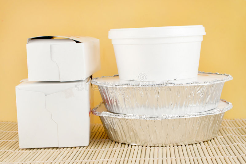 Chinese takeout. Chinese food delivery or takeout aluminum covered containers and cardboard boxes on bamboo placemat stock photos