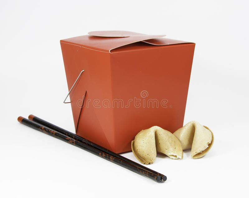 Chinese Takeout, Chopsticks, and Fortune Cookies. Red Chinese takeout box, black and red wooden chopsticks, and two fortune cookies against a white background stock photography