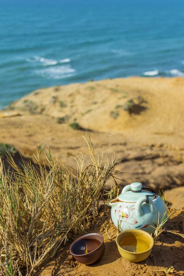 Chinese tea ceremony with porcelain teapot, clay cups. View of nature beach landscape with blue sea on a sunny day royalty free stock images