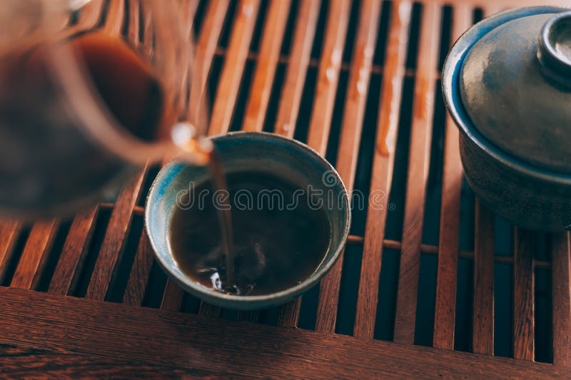 Chinese tea cup is poured by hot fresh black tea stock images