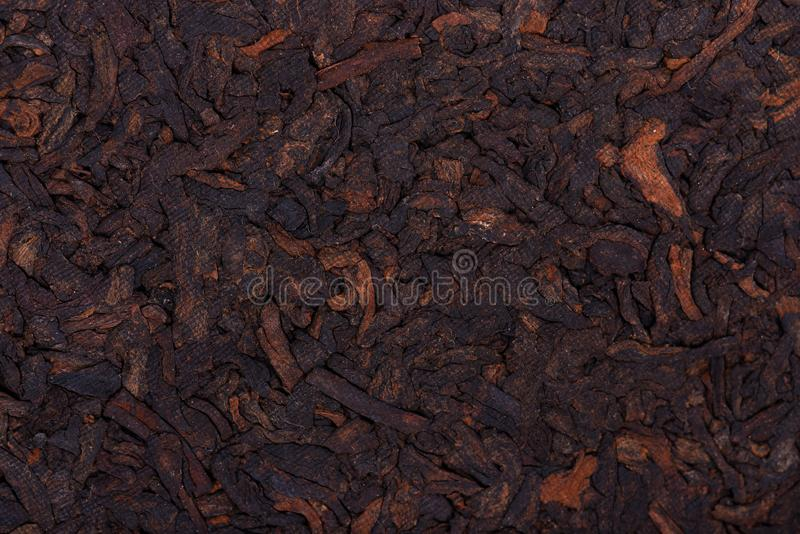 Chinese tea Shou Puer. Pressed fermented Pu-erh tea. Macro close up. Aromatic black puer tea. Healthy drink. Texture. royalty free stock photo