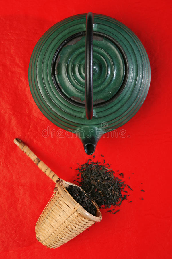 Chinese teapot and a wicker scoop with herb tea le stock image