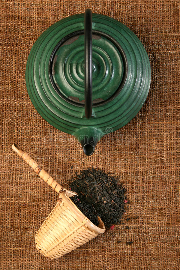 Chinese teapot and a wicker scoop with herb tea le royalty free stock photography