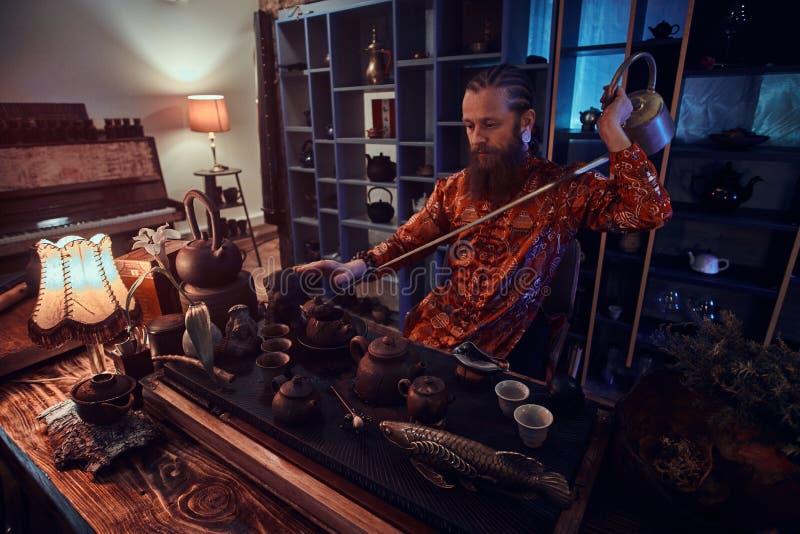Chinese theeceremonie Kaukasische meester die in kimono natuurlijke thee in de donkere ruimte met een houten binnenland maken, di royalty-vrije stock afbeeldingen