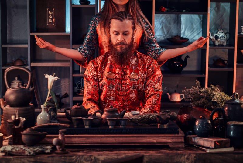 Chinese theeceremonie Paar in oosterse traditionele kleren tijdens een Chinese theeceremonie in de donkere ruimte met a royalty-vrije stock afbeeldingen