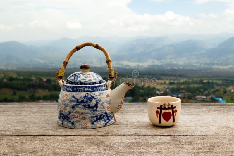 Chinese theepot en kop met groene thee op een houten lijst aangaande een achtergrond van toneelbergenlandschap royalty-vrije stock afbeeldingen