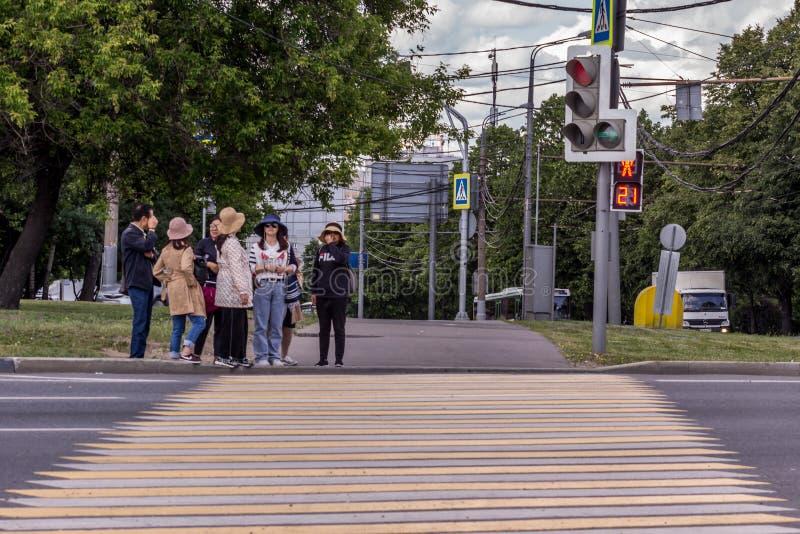 Chinese toeristen die de weg kruisen Groep die mensen zich op het rode verkeerslicht bevinden stock afbeelding