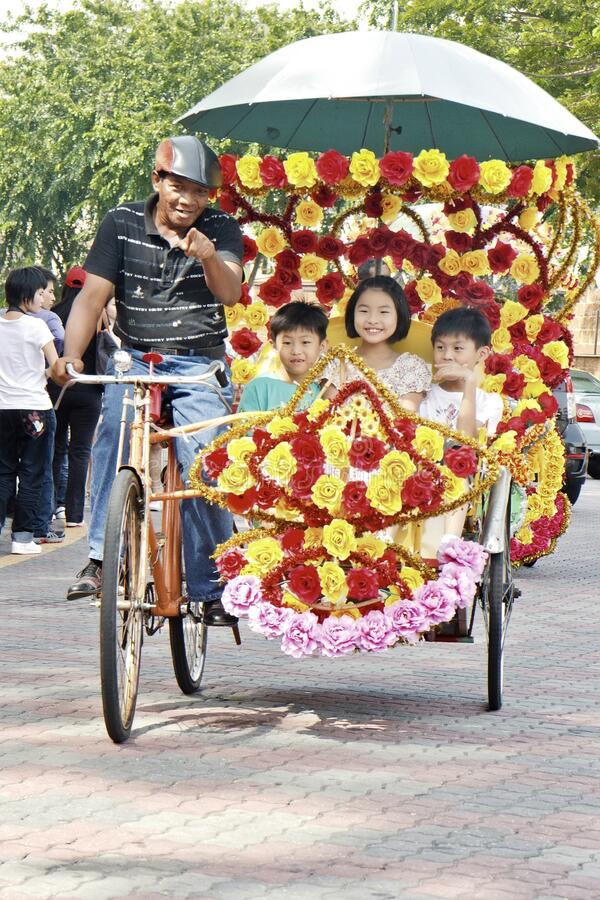 Chinese tourist kids having a sustainable and colorful trishaw ride in malacca. Chinese tourist kids having the most ecological, sustainable, flowerish and royalty free stock photos