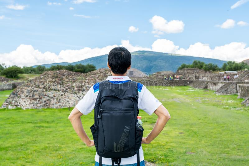 A chinese tourist in the ruins of the architecturally significant Mesoamerican pyramids and green grassland located at at. Teotihuacan, an ancient Mesoamerican royalty free stock photos