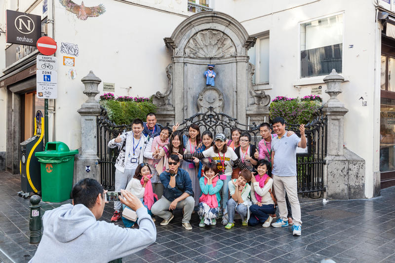 Chinese tourists at the Manneken Pis statue in Brussels. BRUSSELS, BELGIUM - AUG 22: Chinese tourists taking pictures at the Manneken Pis statue in Brussels stock photography