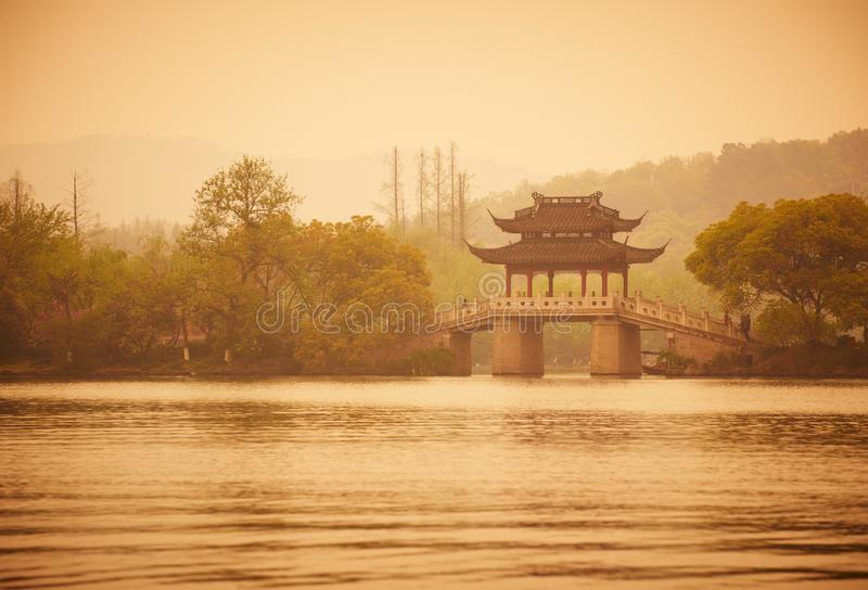 Chinese traditional bridge with pavilion on the coast of West Lake, public park in Hangzhou city, China royalty free stock photo