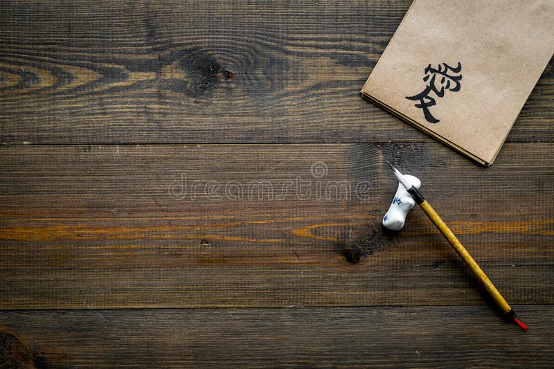 Chinese traditional calligraphy concept. Asian hieroglyph love in craft paper notebook near special writting pen on dark. Wooden background top view royalty free stock photography
