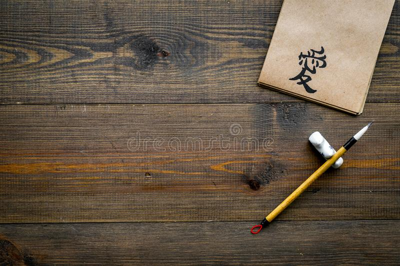 Chinese traditional calligraphy concept. Asian hieroglyph love in craft paper notebook near special writting pen on dark. Wooden background top view royalty free stock image