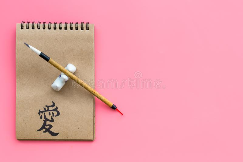 Chinese traditional calligraphy concept. Asian hieroglyph love in craft paper notebook near special writting pen on pink. Background top view stock images