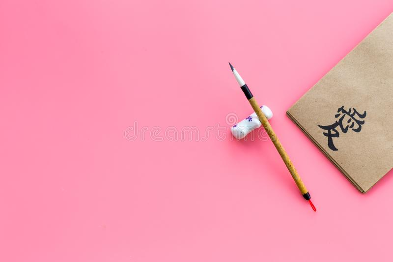 Chinese traditional calligraphy concept. Asian hieroglyph love in craft paper notebook near special writting pen on pink. Background top view stock photography