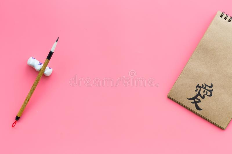 Chinese traditional calligraphy concept. Asian hieroglyph love in craft paper notebook near special writting pen on pink. Background top view royalty free stock photo