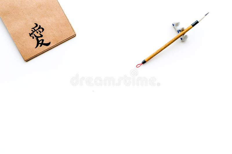 Chinese traditional calligraphy concept. Asian hieroglyph love in craft paper notebook near special writting pen on. White background top view royalty free stock photos