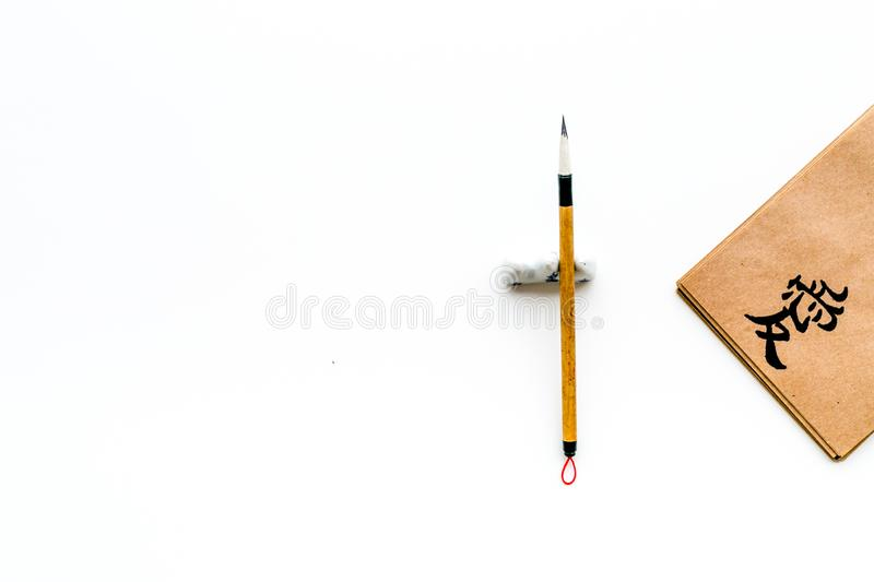 Chinese traditional calligraphy concept. Asian hieroglyph love in craft paper notebook near special writting pen on. White background top view stock images