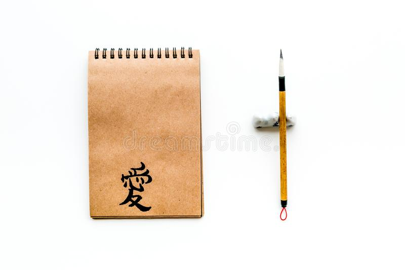 Chinese traditional calligraphy concept. Asian hieroglyph love in craft paper notebook near special writting pen on. White background top view stock image