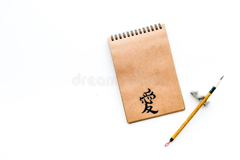 Chinese traditional calligraphy concept. Asian hieroglyph love in craft paper notebook near special writting pen on. White background top view royalty free stock image