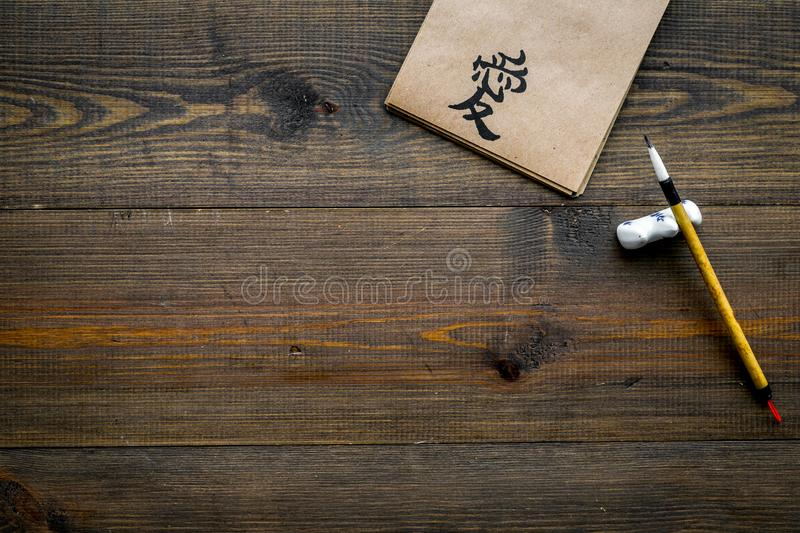 Chinese traditional calligraphy concept. Asian hieroglyph symbol in craft paper notebook near special writting pen on. Dark wooden background top view royalty free stock photos