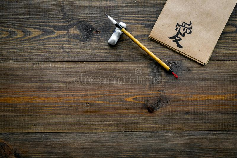 Chinese traditional calligraphy concept. Asian hieroglyph symbol in craft paper notebook near special writting pen on. Dark wooden background top view stock photo