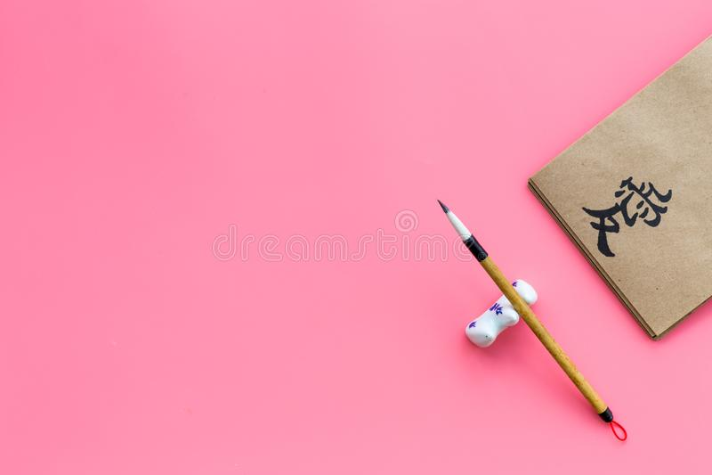 Chinese traditional calligraphy concept. Asian hieroglyph symbol in craft paper notebook near special writting pen on. Pink background top view royalty free stock photo