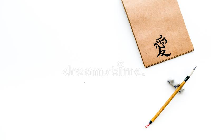 Chinese traditional calligraphy concept. Asian hieroglyph symbol in craft paper notebook near special writting pen on. White background top view royalty free stock photo