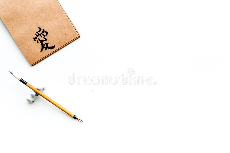 Chinese traditional calligraphy concept. Asian hieroglyph symbol in craft paper notebook near special writting pen on. White background top view stock image