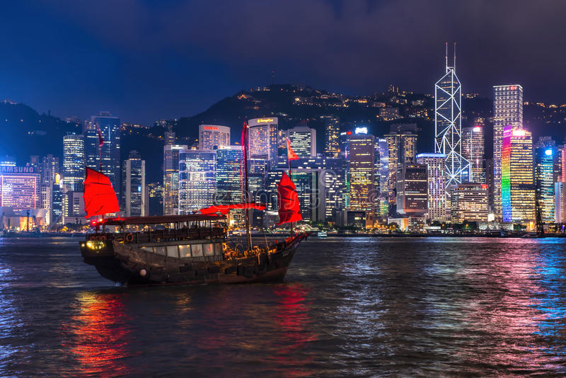A Chinese traditional junk boa sailing passing famous Hong Kong skyline. HONG KONG - JUNE 09, 2015: A Chinese traditional junk boa sailing passing famous Hong stock photo