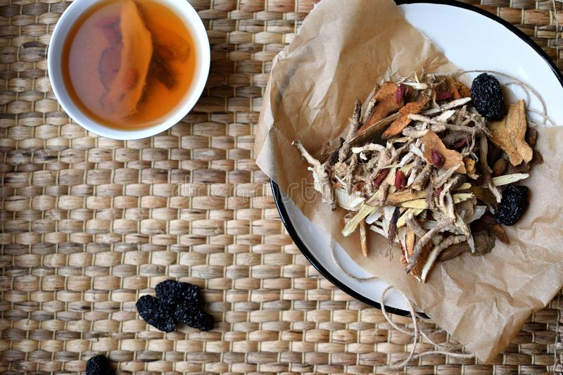 Chinese traditional medicine script. Herbal tea with jujubes, goji berries, gingseng roots and others on parchment paper on neutra. Chinese traditional medicine stock image
