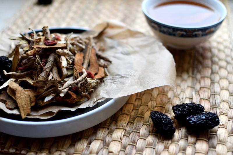 Chinese traditional medicine script. Herbal tea with jujubes, goji berries, gingseng roots and others on parchment paper on neutr. Chinese traditional medicine royalty free stock photos