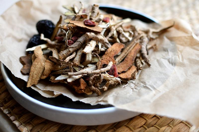 Chinese traditional medicine script. Herbal tea with jujubes, goji berries, gingseng roots and others on parchment paper on neutr. Chinese traditional medicine royalty free stock photography