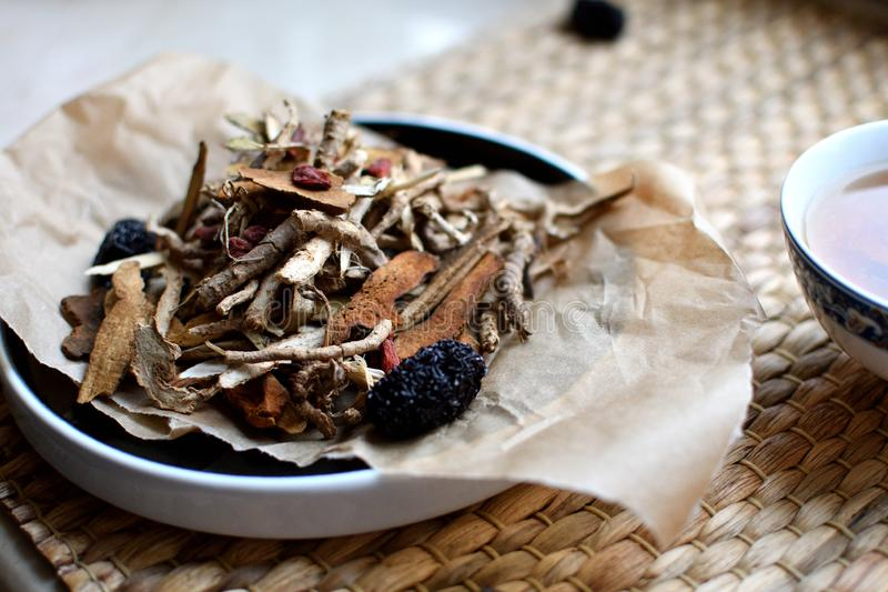 Chinese traditional medicine script. Herbal tea with jujubes, goji berries, gingseng roots and others on parchment paper on neutr. Chinese traditional medicine stock photos