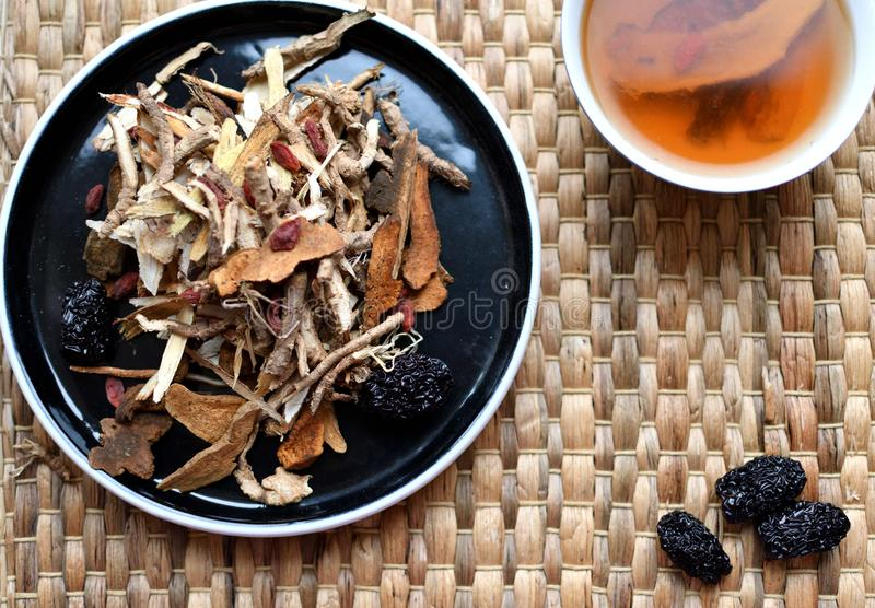 Chinese traditional medicine script. Herbal tea with jujubes, goji berries, gingseng roots and others on parchment paper on neutr. Chinese traditional medicine stock photo