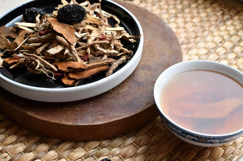 Chinese traditional medicine script. Herbal tea with jujubes, goji berries, gingseng roots and others on parchment paper on neutr. Chinese traditional medicine stock photography