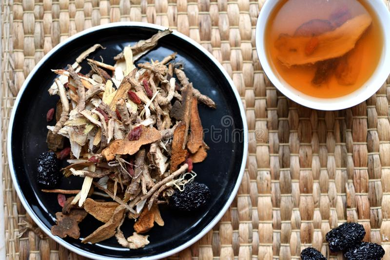 Chinese traditional medicine script. Herbal tea with jujubes, goji berries, gingseng roots and others on parchment paper on neutr. Chinese traditional medicine royalty free stock image