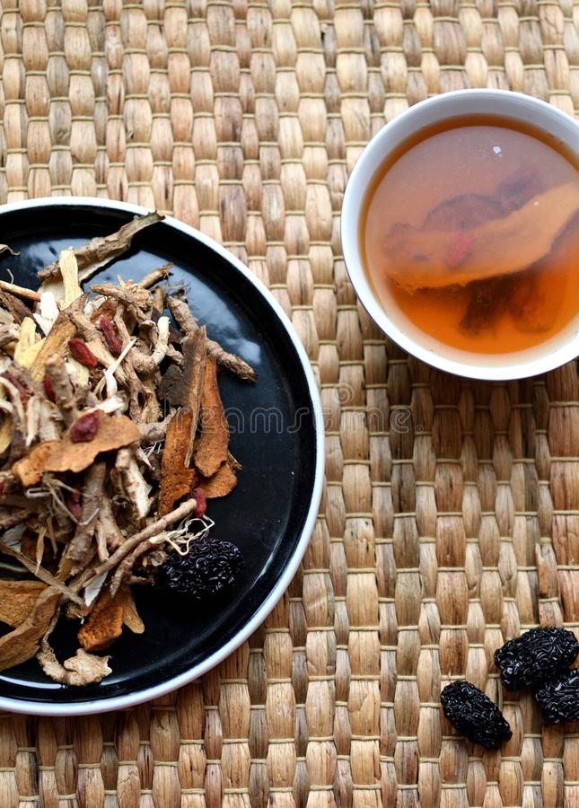 Chinese traditional medicine script. Herbal tea with jujubes, goji berries, gingseng roots and others on parchment paper on neutr. Chinese traditional medicine stock images