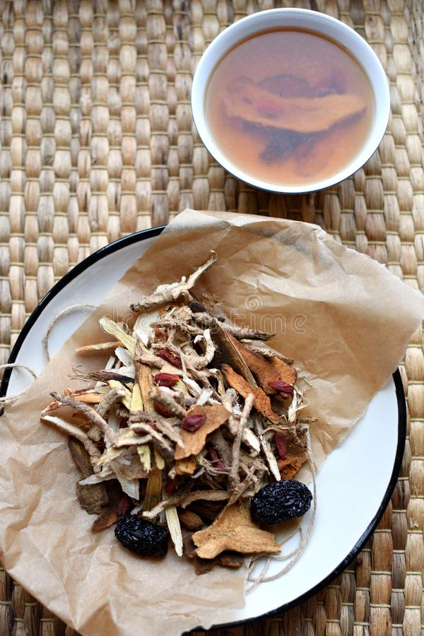 Chinese traditional medicine script. Herbal tea with jujubes, goji berries, gingseng roots and others on parchment paper on neutra stock image