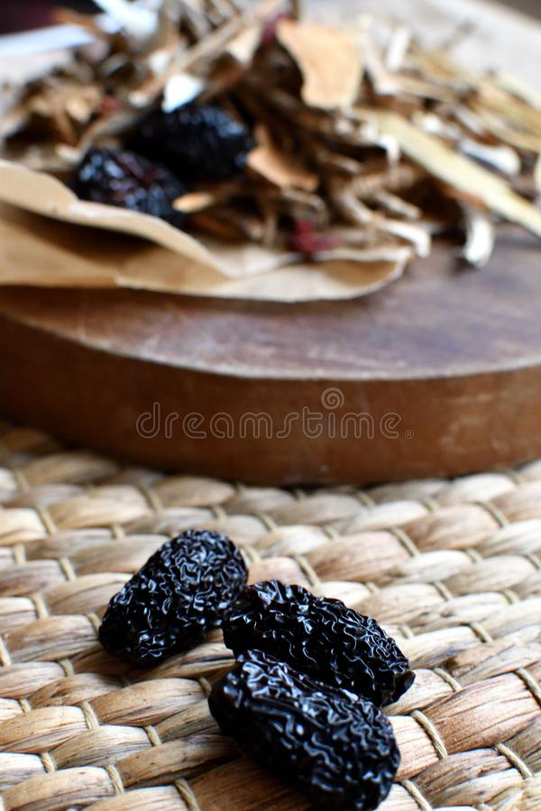 Chinese traditional medicine script. Side view. Chinese traditional medicine script. Herbal tea with jujubes, goji berries, gingseng roots and others on stock photos