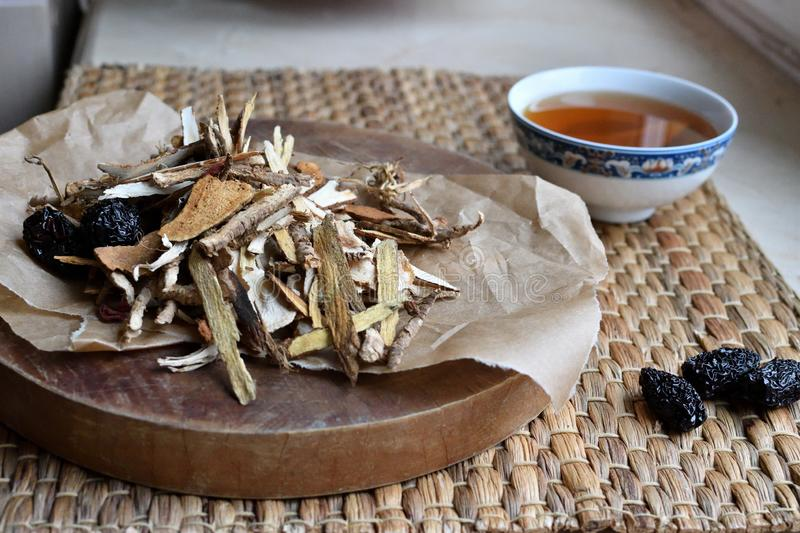Chinese traditional medicine script. Side view. Chinese traditional medicine script. Herbal tea with jujubes, goji berries, gingseng roots and others on stock image